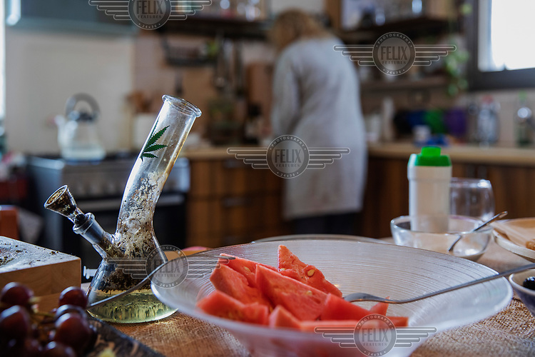 Hagit Yagoda, a medical cannabis activist, who uses the drug to help treat a cancer, smoking the medicinal cannabis using a water pipe in the kitchen of her home.