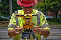 Construction worker sets up a transit for measuring sections of the roadway at the State and Schrock road construction site.