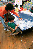 MR/Schenectady, New York.Yates Arts Magnet School/ Pre-Kindergarten.Aide (African-American) with students using shaving cream as art and sensory experience. (Students aged 4-5, including Hispanic and African-American)..MR:YS-9-Pk      FC#:20910-00419.scan from slide.© Ellen B. Senisi