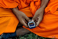 A Buddhist Monk in Cambodia is using his Cellphone for texting