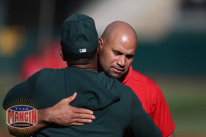 OAKLAND, CA - SEPTEMBER 4:  Coach Rickey Henderson #24 of the Oakland Athletics hugs Albert Pujols #5 of the Los Angeles Angels during batting practice before the game at the Oakland Coliseum on Wednesday, September 4, 2019 in Oakland, California. (Photo by Brad Mangin)
