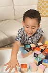 Two year old toddler boy talking and pointing at wooden alphabet block
