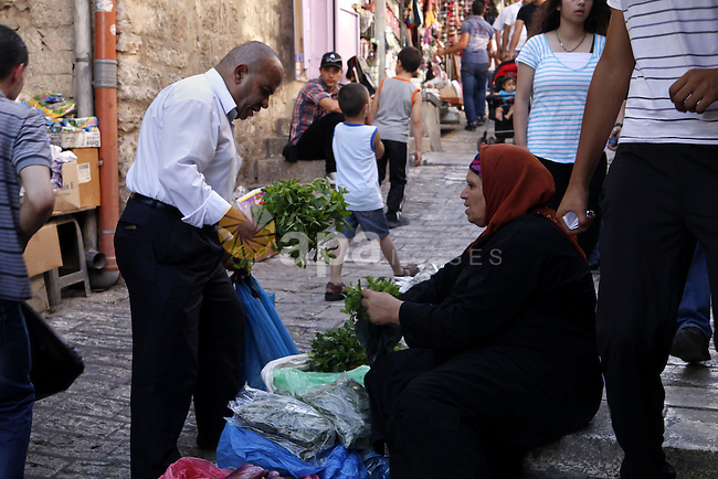 A Palestinian woman sells greens at the market of Damascus gate near al-Aqsa mosque in Jerusalem's Old City, June 26, 2013. Photo by Saeed Qaq