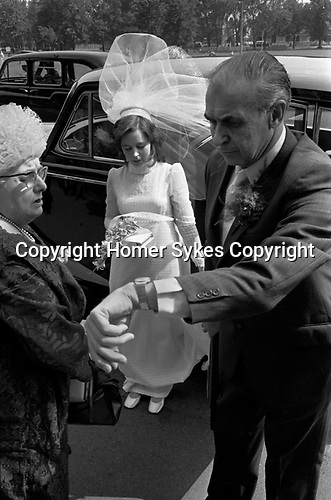 The bride, in white wedding gown and parents arrive at church by taxi, father checks watch for the time, are we late or early? London 1970s.