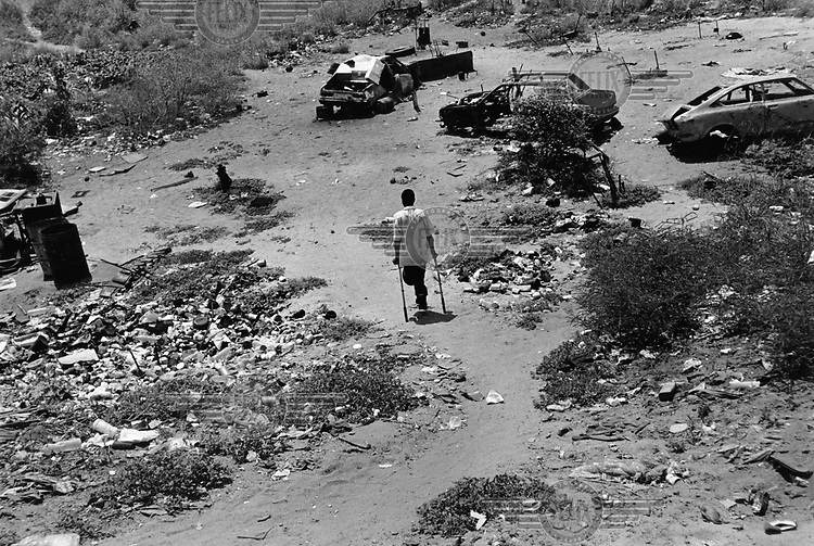 21 year old Joao, who lost a leg fighting UNITA (National Union for Total Independence of Angola) wanders across an area of wasteland...