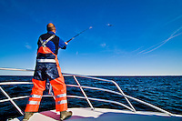 A fisherman in his 40s is casting a top water lure from the bow of a sport fishing boat, in the waters in front of the Cape Cod peninsula
