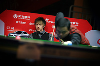 CHINA. Beijing. Snooker players Judd Trump (UK) and Tang Jun (China) during the China Open.  Snooker is a cue sport played on a large table measuring 3.6 metres x 1.8 metres. Originating in India in the late 19th Century where it was invented by British Army officers, the game has been a mainstay in British sport over the past few decades. Recently however, popularity of the sport has declined as the sport struggles to compete with other popular sports. The sport is however flourishing in countries such as China, where it is now the second most popular sport, behind Basketball. In a country where the  players are treated like movie-stars, China may be the great hope for the sports recovery. 2009