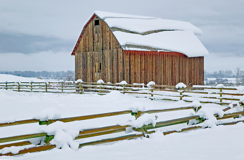Barn with fence and snow slipping on roof. Near Halfway, Oregon