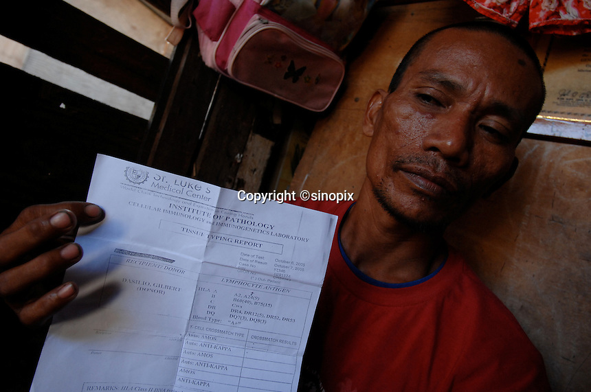Kidney trader Juanlerio Avila, 38, shows the copy of a tissue typing from from one his clients who is waiting for the call to donate his kidney. Avila, 38 has introduced 70 men to his conatct in recent years and recieved about 10,000 pesos (113 pounds) each time. Men from the Basico port area slum of Manilasell their kidney's for between 70,000 -  90,000 pesos (800 - 1030 pounds).  More than 300 have sold their kidneys in this slum of 16,000 people.<br />
