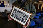 Glossop North End 0 Barnoldswick Town 1, 19/02/2011. Surrey Street, North West Counties League Premier Division. Glossop North End director Stewart Taylor showing off an archive photograph of Glossop North End in the clubhouse of the club's Surrey Street ground before their game with Barnoldswick Town in the Vodkat North West Counties League premier division. The visitors won the match by one goal to nil watched by a crowd of 203 spectators. Glossop North End celebrated their 125th anniversary in 2011 and were once members of the Football League in England, spending one season in the top division in 1899-00. Photo by Colin McPherson.