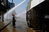 """Santiago, Chile<br /> October 1988<br /> <br /> An anti-Pinochet protester defies a government water-cannon prior to the plebiscite.<br /> <br /> In October 1988, General Augusto Pinochet ordered a plebiscite vote asking Chilean citizens whether he should continue in office. It produced a decisive """"no"""" vote and the following year he lost the first presidential election in 19 years. However, under a constitution crafted by his advisors, he remained as army commander until 1998. <br /> <br /> Pinochet continued to wield enormous power until his arrest in London on human rights charges in October 1998."""