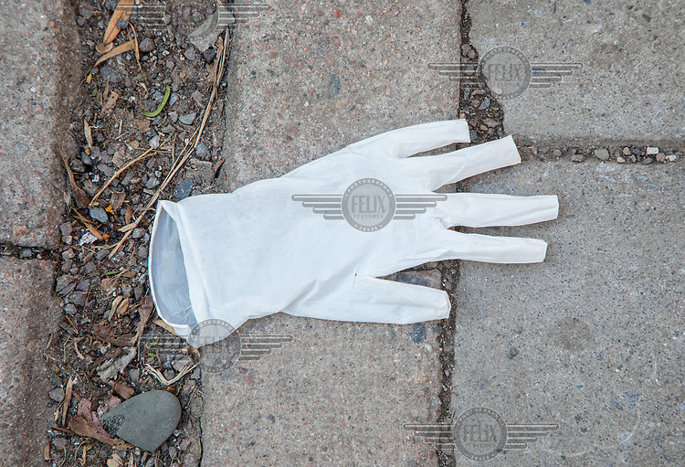 Discarded protective glove on a sidewalk. Norwegian authorites introduced measures to combat the Coronavirus (COVID-19).<br />