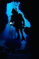 Scuba diver entering underwater cave with flashlight. Anacapa Island, CA
