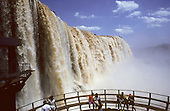 Iguassu Falls, Brazil. Huge cascade with people sitting in a semi-circular viewing area in the foreground.