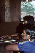 A-Ukre, Brazil. Two Kayapo Indian warriors with intricate black genipapo face paint with a book on the table. Para State.
