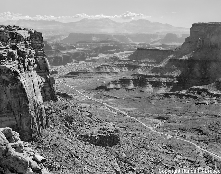 """""""Shafer Trail Road""""<br /> Canyonlands National Park, Utah<br /> <br /> The Shafer Trail Road is a dirt/gravel road 19 miles long that is mostly wide enough for only one vehicle and offers breathtaking views of scenery in the Islands in the Sky District of Canyonlands NP. Much of the Shafer Trail Road is very steep and this photograph was acquired from a steep section of the road although the photo only shows a relatively flat section of the road far below. Driving Shafer Trail Road requires steady nerves and a steady hand on the wheel but it provides fabulous views of Utah scenery."""