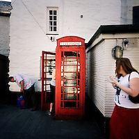 Tourists in a red telephone box in the village of Polperro, Cornwall.