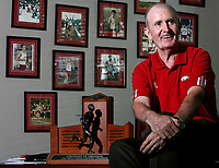 Arkansas Democrat-Gazette/DAN HALE - University of Arkansas Track Coach John McDonnell sits with one of his 83 conference championship trophies inside his office at Bud Walton Arena on Tuesday afternoon in Fayetteville. 5-13-08 focus nw