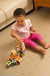 18 month old toddler girl at home, playing with blocks stacking them into tower