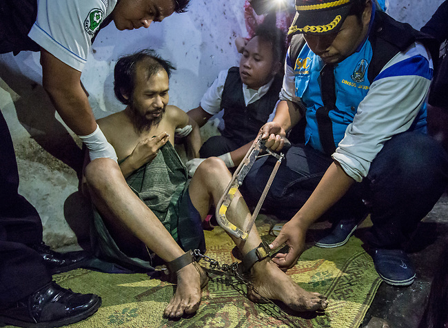 """5 April 2017, Surabaya,East Java,Indonesia: Ubaidilah a 44 year old mental illness sufferer is released (using a hacksaw) from the chains he has been shackled to in a dingy room next to his family home in Badal Pandean village, East Java. Indonesian Social Affairs Dept. workers cut the bonds, cut his hair and nails and washed his emaciated body before putting him in a strait jacket and taking him to a facility in Malang for treatment. Ubaidilah is a patient in a program called """"E- Shackling"""" which aims to free people suffering from mental illness, from the shackles that family often place them in to control them in the wake of a lack of treatment options and the program will treat them and enter them in a data base allowing them to be traced before releasing them back to their families. Some people stay chained to a stake or in rooms for years by their families and not all families are willing to take their sick family members back. Picture by Graham Crouch/The Australian"""