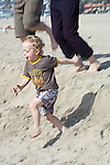 blonde male child jumps and runs down sand dune on beach