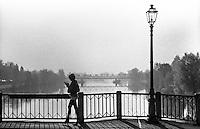 Pizzighettone (Cremona). Un lampione e una donna che attraversa il ponte sull'Adda mentre adopera il telefono cellulare --- Pizzighettone (Cremona). A lamppost and a woman crossing the bridge over the river Adda while operating her cell phone
