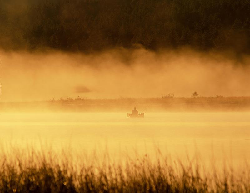 Fly fisherman on Davis Lake with fog. Oregon