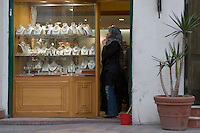 Tripoli, Libya - Libyan Woman in Jeans Looking at Jewelry Necklaces in the Medina (Old City).  Using Cell Phone.  Calling her Husband?
