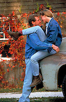 Couple enjoy each other's company on an autumn day with their old pickup truck.