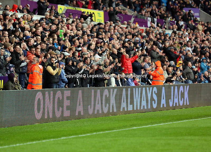 Sunday, 26 April 2014<br /> Pictured: Swansea supporters applaud for former player Ferrie Bodde on the sixth minute, while messages on the LED screens wish him well.<br /> Re: Barclay's Premier League, Swansea City FC v Aston Villa at the Liberty Stadium, south Wales.