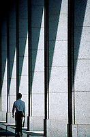 A Japanese office worker walks amongst the shadows cast by columns in the Shinjuku business district. Tokyo, Japan.