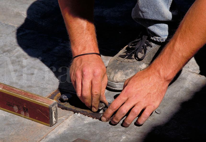 Hands and metal bolts, concrete slab, horz. West Hartford CT USA.