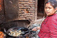 Nepal, Patan.  Street Food Vendor Frying Mo-mo Dumplings.