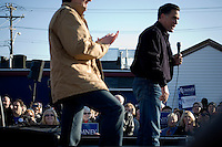 """Former governor of Minnesota and Republican presidential candidate Tim Pawlenty (brown jacket) stands with  Republican presidential candidate Mitt Romney, former governor of Massachusetts, as he speaks during a rally in Manchester, New Hampshire, on Sat. Dec. 3, 2011. The rally was called, """"Earn It with Mitt,"""" and was designed to bolster local efforts to help Romney """"earn"""" voters' support for the upcoming Republican primary."""