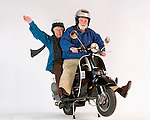 An older couple posed on a motor scooter on a white background.