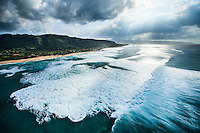 An aerial view of waves rushing towards the North Shore of O'ahu.