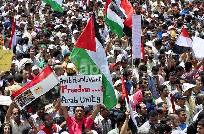 """Egyptian demonstrators wave a Palestinian flag during a rally at Cairo's Tahrir Square on May 13, 2011 during a protest calling for national unity after attacks on Egyptian churches, and solidarity with the Palestinians as they mark the """"Nakba"""" or """"catastrophe"""" which befell them following Israel's establishment in 1948. Photo by Ahmed Asad"""