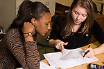Education High School mathematics two female students working together calculator nearby