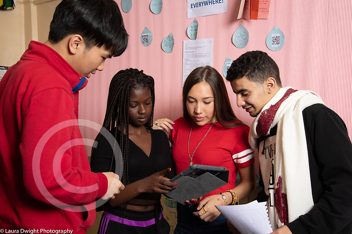 Education High School group of female friends in corridor of male and female students talking and looking at tablet one holds