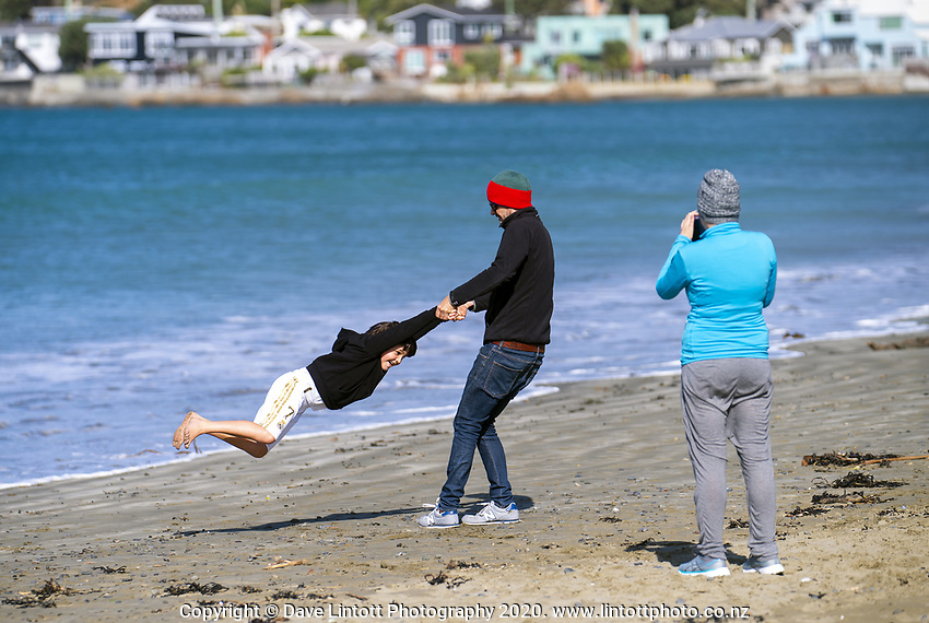 People walk on Lyall Bay beach on Easter Monday during lockdown for the COVID19 pandemic in Wellington, New Zealand on Monday, 13 April 2020. Photo: Dave Lintott / lintottphoto.co.nz