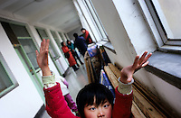 CHINA. Beijing. A child playing in an orphanage outside of Beijing. The orphanage is a mix of orphans and children left for long periods of time by migrant workers who cannot take their children with them. There are currently millions of orphans in China living in orphanages spread throughout the country. As a result of China's one-child policy, many children are abandoned or given up if they suffer from any physical or mental handicap as the parents strive to have a child born 'normal' and well. This has led to may children being abandoned to live in state and privately-owned orphanages.