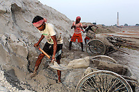 Workers dig sand on the grounds of a brick making factory on the outskirts of Kolkata.<br />