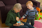 20 month old toddler boy with grandmother, pretend play, feeding doll with spoon;child care grandmother takes care of grandchildren twice a week