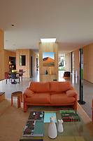 The open plan living area features a Vico Magistretti sofa and the walls are clad in pine