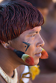 Xingu Indigenous Park, Mato Grosso State, Brazil. Aldeia Waura. Djalaó Waura with feather ear plugs and hair coloured with urucum.