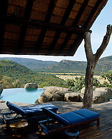A pair of sun-loungers is placed in the shade beside one of three swimming pools at the lodge overlooking the spectacular landscape