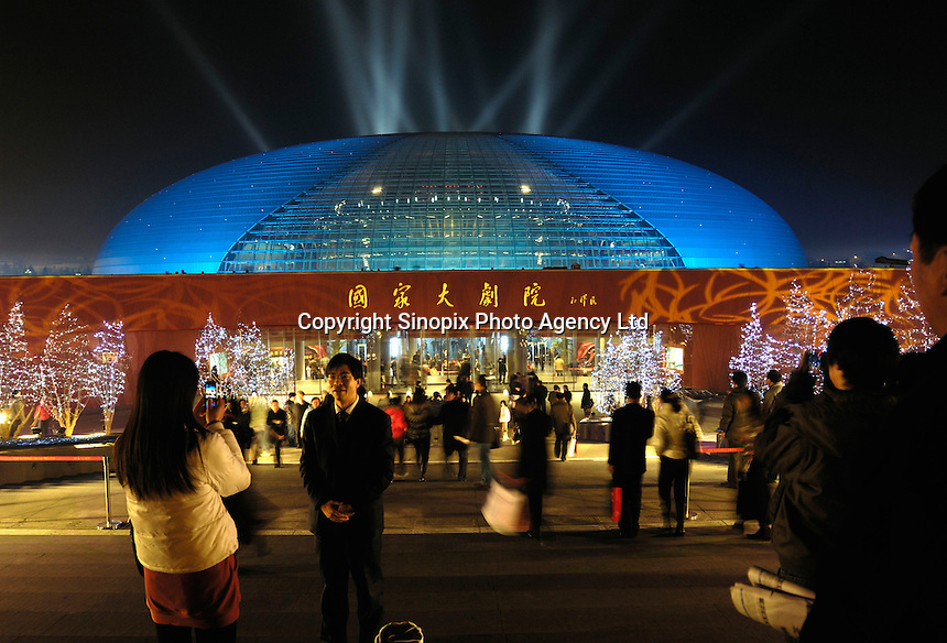 Tourists take pictures in front of the National Grand Theatre designed by French architect Paul Andreu, beside the Great Hall of the People in Beijing, China..