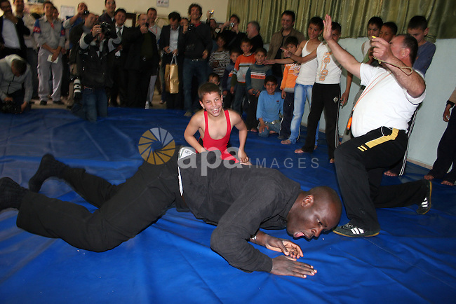 Former French football player Lilian Thuram plays with a Palestinian boy and a referee following a wrestling game at the Tareq Ben Ziad Club in the West Bank city of Hebron on April 13, 2011. Thuram is visiting the Palestinian territories in support of the education programme funded by France through the United Nations Relief and Works Agency (UNRWA).Photo by Najeh Hashlamoun