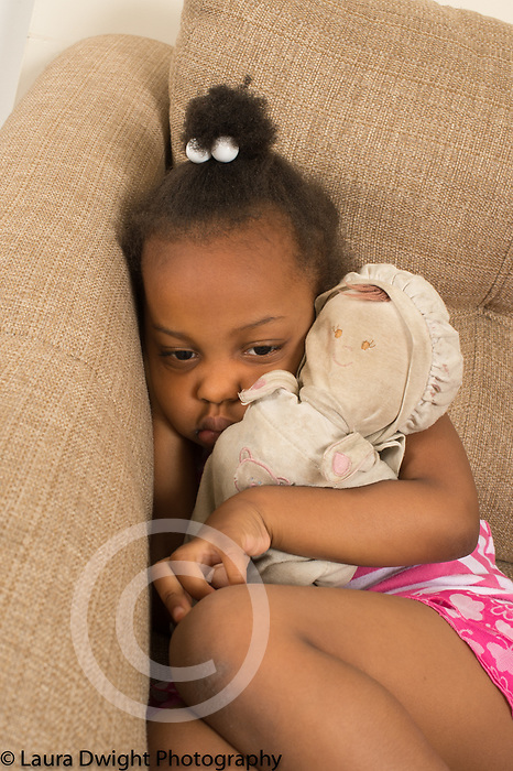 3 year old girl on couch at home quiet sad moment hugging favorite worn soft stuffed doll toy
