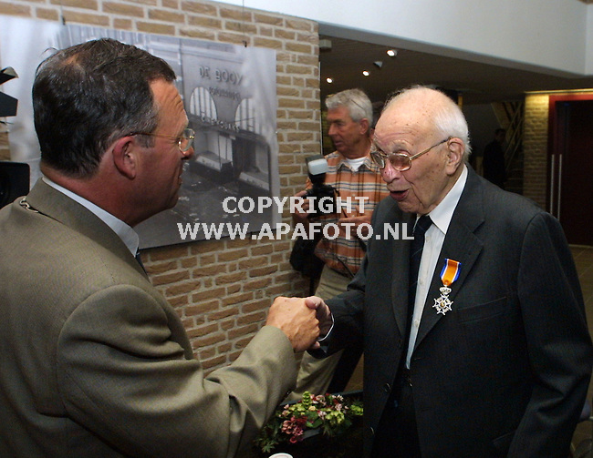 duiven 030501 burgemeester zomerdijk en oud fotograaf, de 102-jarige p.j.de booijs nadat laatstgenoemde als oudste onderscheiden nederlander,  een lintje kreeg voor zijn fotografisch werk in arnhem tijdens de laatste dagen van de oorlog .op de achtergrond een foto uit de tentoonstelling van zijn werk met daarop de fotowinkel van waaruit hij in de oorlogsjaren werkte.<br />foto frans ypma APA-foto